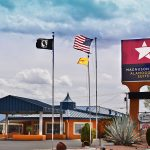 outside of Magnuson Hotel & Suites Alamogordo with flags
