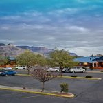 exterior of Magnuson Hotel & Suites Alamogordo with stone mountain in distance