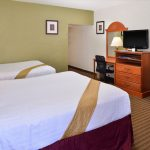 Two queen beds with TV, nightstand, and mini fridge at Magnuson Hotel & Suites Alamogordo