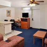 kitchenette suite with coffee table, arm chair, sofa, and TV at Magnuson Hotel & Suites Alamogordo