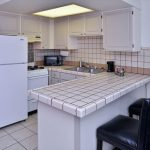 suite kitchen with full refrigerator, bar stool, and counter at Magnuson Hotel & Suites Alamogordo