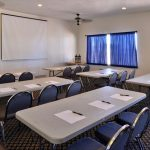 meeting room with tables and blue chairs at Magnuson Hotel & Suites Alamogordo